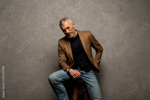 businessman in jeans and blazer sitting on stool and looking at camera on grey Canvas Print