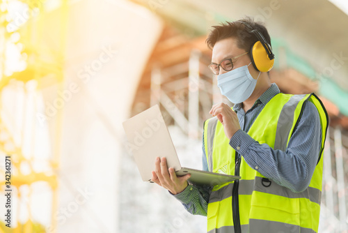 Obraz smart asian male wearing protection face mask professional civil engineer hand hold laptop site construction check with infastrcture and building background - fototapety do salonu