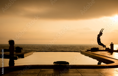 Silhouette Woman Jumping In Swimming Pool By Sea Against Sky During Sunset Wallpaper Mural