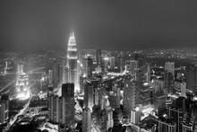 Illuminated Petronas Towers Amidst Buildings At Night