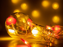 Large Decorative Light Bulb With Lights In The Form Of Hearts. Photo With Bokeh. Greeting Card