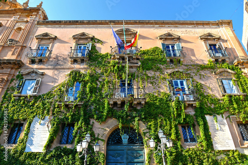 facade detail of city hall building in the historic center of Agrigento overgrown with ivy, door and windows and decoration Canvas Print