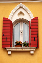 Close-up Of A Window With Gothic Arch And Open Red Shutters On An Orange Wall. Caorle, Venice Province, Veneto, Italy, Europe