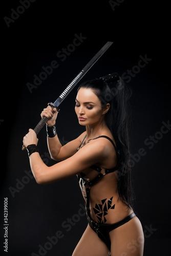 Foto Sensual female warrior in underwear swinging sword