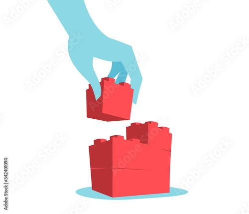 Fotografía La mano che costruisce il muro con mattoncini