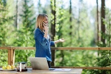 Side View Medium Shot Of Smiling Young Woman Talking On Cell Phone Standing On Wooden Balcony Of Country House, Open Laptop On Table