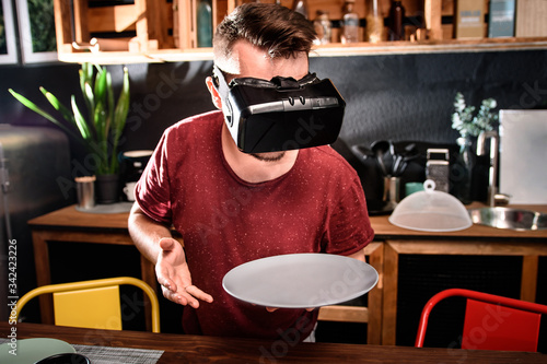 Valokuvatapetti Young guy wearing virtual reality glasses in the kitchen