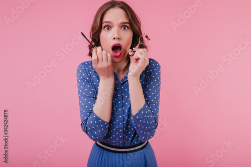 Nerveous wonderful girl with mascara and eyelash curler posing with mouth open Wallpaper Mural