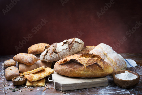 Fotografie, Obraz Assorted bread on wooden background. Space for text.