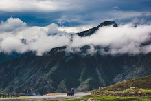A Car Drives Along A Road Along A Mountain Range In The Ongudaysky District Of The Altai Krai, Russia