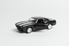Black Toy Car With An Open Door With Red Stripes On The Hood