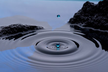 Gotas De Agua Color Azul Congeladas En El Aire Y Formando Ondas En La Superficie Liquida, Con Rocas O Piedras Al Fondo.
