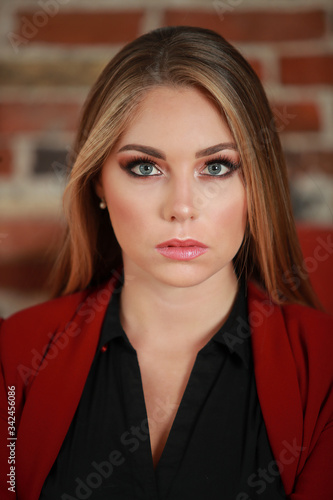 Fotomural Portrait d'une jolie femme blonde en veste de tailleur chez elle