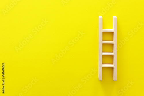 wooden ladder over yellow background Canvas Print