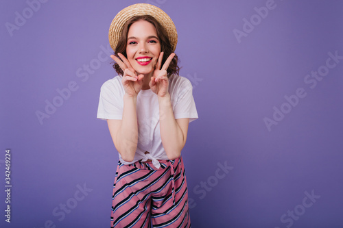 Carefree dark-haired girl posing with happy face expression on purple background Fototapet