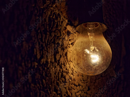 Photo Light bulb on a dark rough stone background