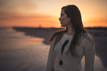 Young Woman Looking Away While Standing On Sea Shore At Beach During Sunset