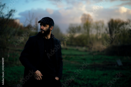 Artistic portrait of a dark-haired man with a beard smoking a cigarette on nature Fototapet
