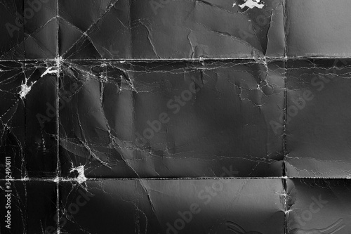 Crumpled black paper with wrinkles and rubbed corners. Old wrapping dusty cardboard