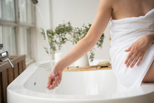 Woman Wrapped In White Towel Sitting On The Edge Of Bathtub And Touching Flowing Water