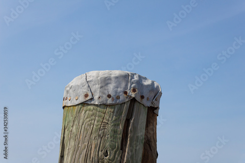 Old metal piling cap hand formed and nailed into the top of a treated wood pilin Canvas Print