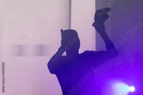 Obraz Zdjęcie rapera w negatywie, sylwetka muzyka odcięta na tle silniejszego światła. - fototapety do salonu