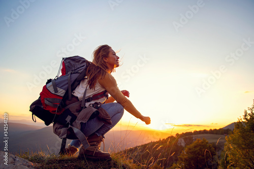 Fototapeta Portrait of happy young woman hiking in the mountains