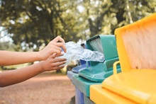 Cropped Image Of Hands Throwing Crushed Bottles In Recycling Bin