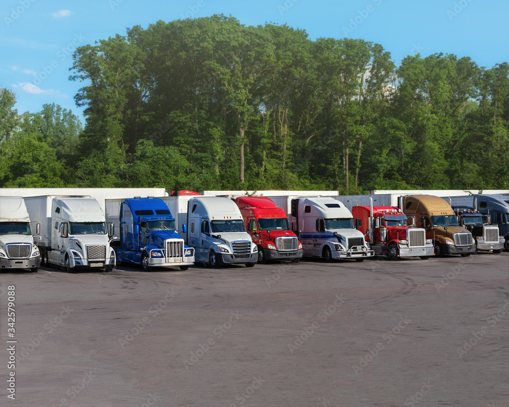 Fototapeta Modern trucks of various colors and models  transportation of different kinds of commercial goods stand in row on truck stop parking lot for truck driver rest according to log book.