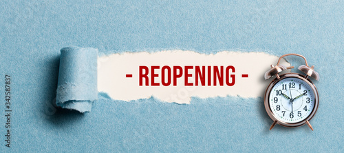 Fotografía torn paper revealing the word REOPENING on white background