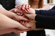 Group of people in suits crossed hands in pile for win closeup. White collar leadership high five cooperation initiative achievement corporate life style friendship deal heap stack concept