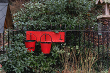 Red Fire Buckets Hanging On Railing By Plants