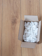 A Cardboard Box With Packing Foam Pellets Top View, On Wooden Floor