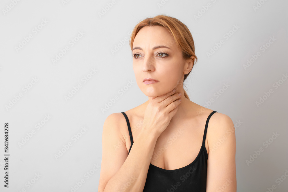 Fototapeta Woman with thyroid gland problem on grey background