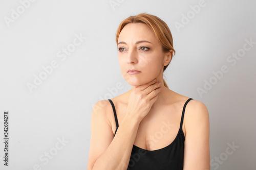 Fototapeta Woman with thyroid gland problem on grey background obraz