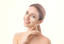 Young Woman With Sun Protection Cream On Face Against White Background