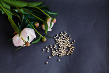 High Angle View Of Beads And Flowers On Gray Background