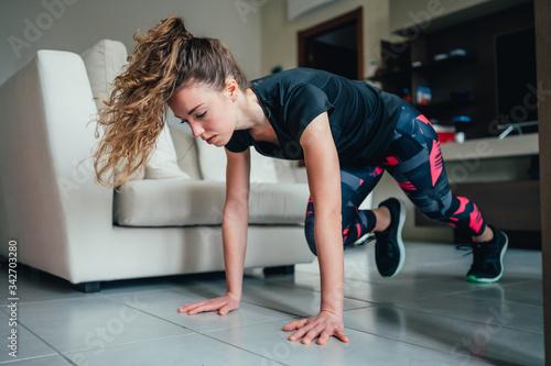 Photo giovane bella ragazza fa sport a casa eseguendo esercizi a corpo libero