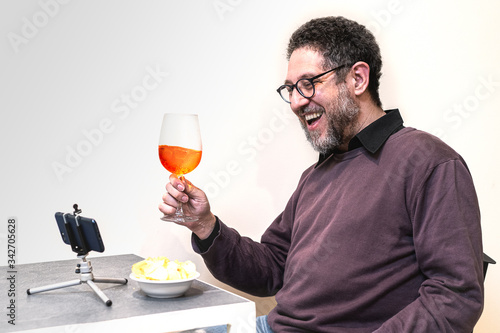 Fotografering mid aged man holding a glass with a spritz cocktail making a video party aperitif online with friends online during quarantine staying at home during lockdown for coronavirus emergency