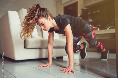 Giovane bella ragazza realizza esercizi fisici a casa Canvas Print