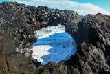 Ocean wave with foam breaks on the coastal rocks in Iceland