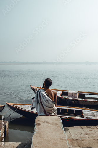Photo Indian man shot from behind sitting crossed legged on the floor in front of the Holy River ganges