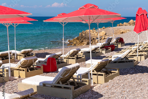 Платно Sun loungers with umbrellas on Ellie beach in Rhodes town. Greece