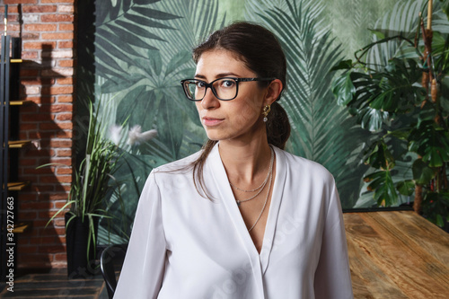 Young sexy women in glasses standing in modern appartment by wooden table Canvas Print