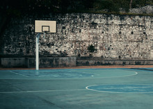 An Old And Abandoned Basketball Court In A Park