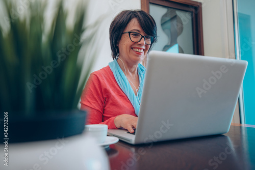 Sixty year old female teacher wearing headphones having online class via video chat on laptop computer Canvas Print