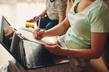 Young Woman With Child Studying On Laptop, Making Notes