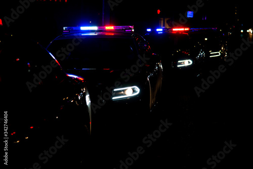 Police cars lined up on the street with their emergency lights on Canvas Print