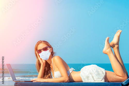 beautiful and sexy young woman lies and rests on a deckchair with a laptop of the sea. woman freelancer with laptop in the resort