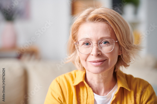 Fototapety, obrazy: Smiling mature female in eyeglasses and casualwear standing in front of camera